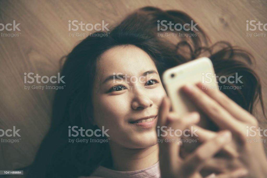 asian woman using smart phone at home asian woman using smart phone at home Adult Stock Photo