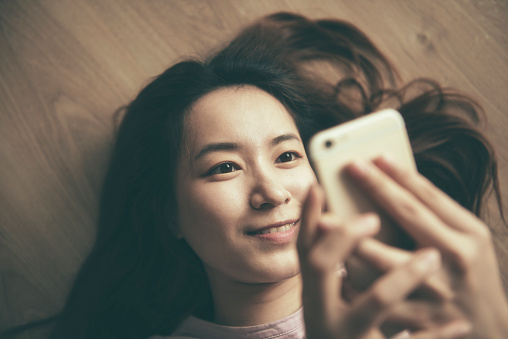 Asian Woman Using Smart Phone At Home Stock Photo - Download Image Now