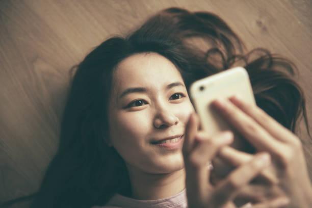 アジアの女性がスマートフォンを使用して自宅で - スマホ 女性 ストックフォトと画像
