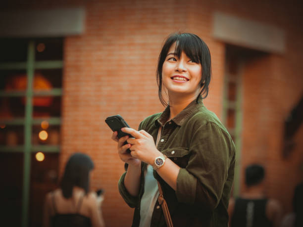 asian woman using smartphone with happy mood smile face  in shopping mall - online shopping imagens e fotografias de stock