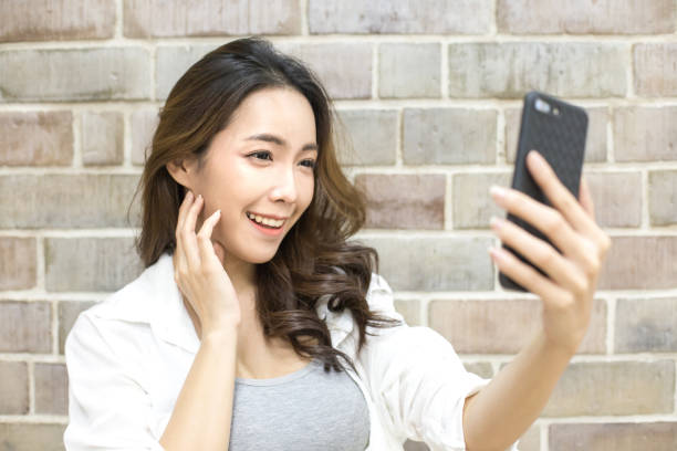 Asiatische Frau mit Smartphone mit Wand Hintergrund lächelt. Frau mit Smartphone für Selfie oder video-Anruf in den sozialen Medien. Menschen mit Technologie-Konzept. – Foto