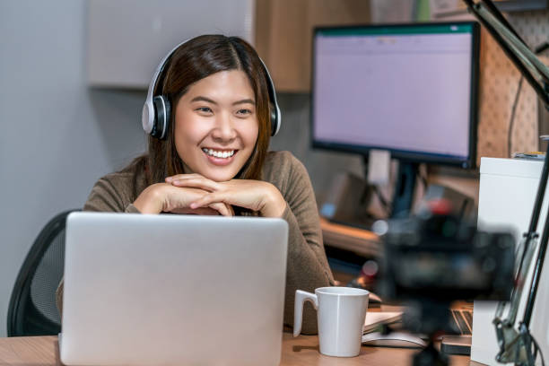 Asian woman using technology laptop and working from home in bedroom