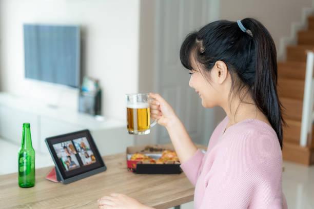 aziatische vrouw virtuele happy hour meeting party en het drinken van alcohol bier online samen met haar vriend in video conferentie met digitale tablet voor een online vergadering in video-oproep voor sociale distantiëring voor infectie risico. - happy hour stockfoto's en -beelden
