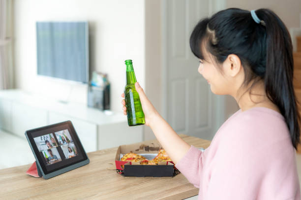 Asian woman virtual happy hour meeting party and drinking alcohol beer online together with her friend in video conference with digital tablet for a online meeting in video call for social distancing for infection risk. Asian woman virtual happy hour meeting party and drinking alcohol beer online together with her friend in video conference with digital tablet for a online meeting in video call for social distancing for infection risk. avoidance stock pictures, royalty-free photos & images