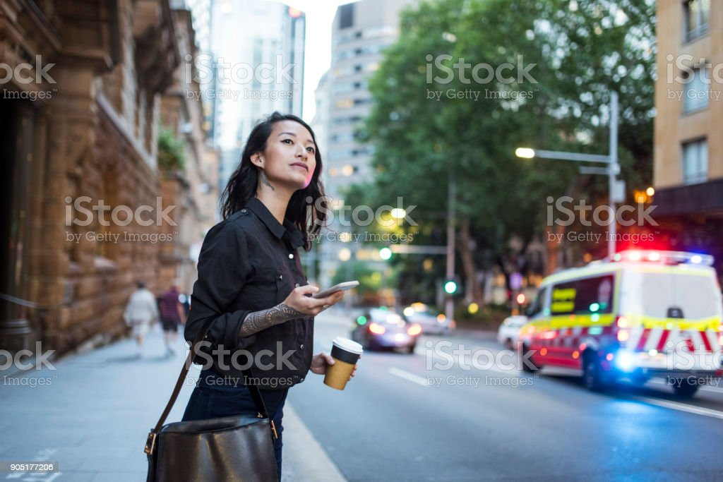 Asian woman waiting for an uber and drinking coffee stock photo