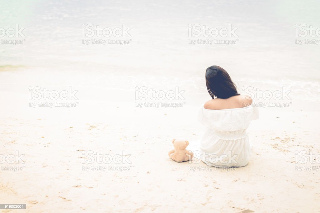 Asian woman waiting for love or somethings that make her happy. Lonely and Beauty concept. Back view scene of girl. Ocean and sea theme. Copy space in left side. Soulmate theme. stock photo