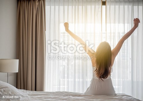istock Asian woman wake up in the morning, sitting on white bed and stretching, feeling happy and fresh 870048184