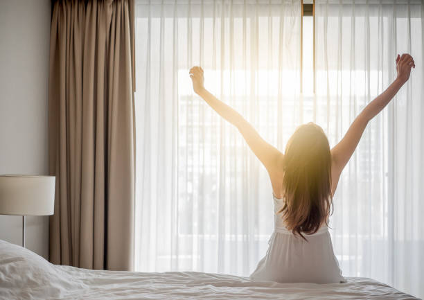 Asian woman wake up in the morning, sitting on white bed and stretching, feeling happy and fresh - foto stock