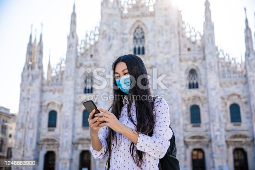 Young beautiful girl walking around in Milan with wearing a face pollution mask to protect herself from the coronavirus.