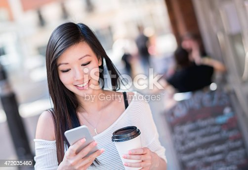 istock Asian woman walking on the street and texting 472035460