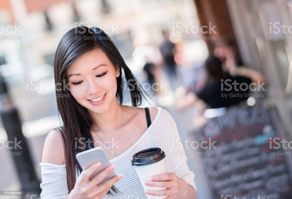 Asian woman walking on the street and texting stock photo