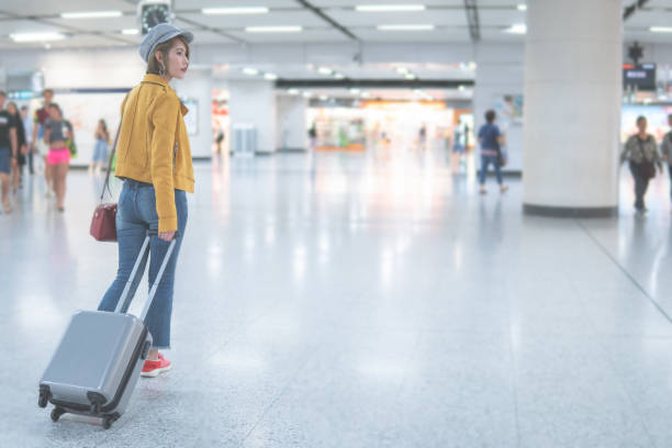 asian woman  walking with suitcase on the airport terminal,travel concept - phone, travelling, copy space imagens e fotografias de stock