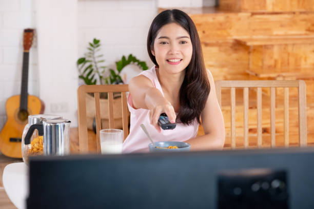 asian woman wathcing tv on demand and use remote control change television channel at breakfast in morning stock photo