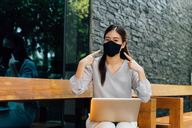 Asian woman wearing a face mask outside while sitting on laptop and pointin at her mask. Don't forget to wear a mask and face mask requirement to go outside concept stock photo