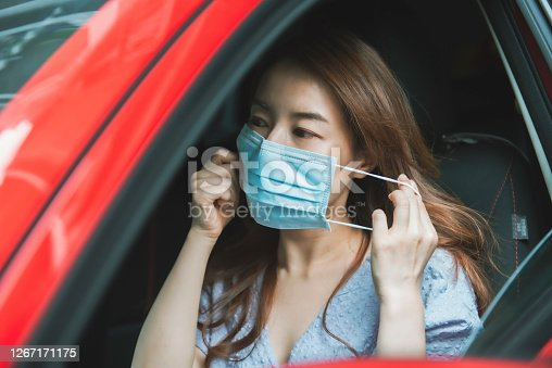 Asian woman wearing a mask on the car