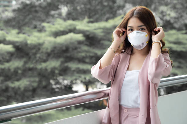 Asian woman wearing a protective face mask for plague coronavirus. Facial hygienic mask for safety outdoor environmental awareness or virus spread concept Asian woman wearing a protective face mask for plague coronavirus. Facial hygienic mask for safety outdoor environmental awareness or virus spread concept deathly stock pictures, royalty-free photos & images