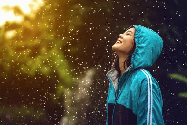 azjatka ubrana w płaszcz przeciwdeszczowy na świeżym powietrzu. jest szczęśliwa. - deszcz zdjęcia i obrazy z banku zdjęć
