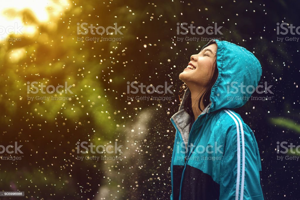 Asian woman wearing a raincoat outdoors. She is happy. - fotografia de stock