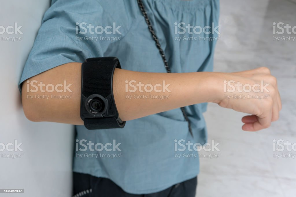 Asian woman wearing black elbow brace with adjustable button to reduce pain on white background stock photo