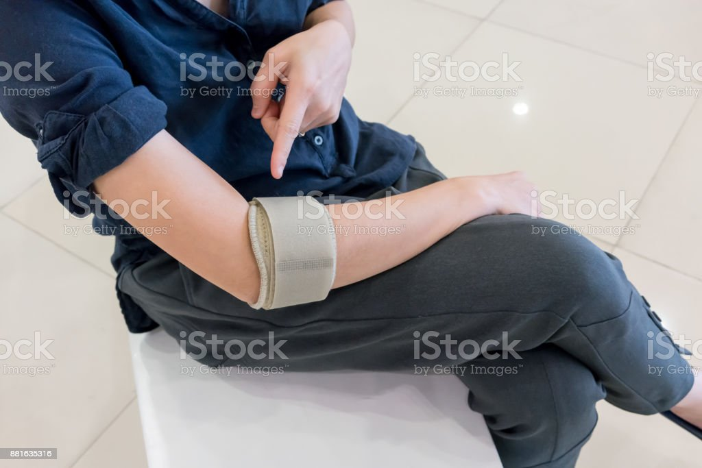 Asian woman wearing elbow brace to reduce pain stock photo