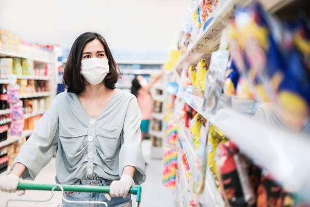 Asian woman wearing face mask and rubber glove push shopping cart in suppermarket departmentstore. Girl choosing, looking grocery things to buy at shelf during coronavirus crisis or covid19 outbreak. Asian woman wearing face mask and rubber glove push shopping cart in supermarket department store. Girl choosing, looking grocery things to buy at shelf during coronavirus crisis or covid19 outbreak. thailand mall stock pictures, royalty-free photos & images