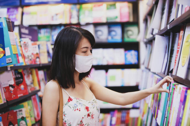 Asian woman wearing face mask choosing book magazine in book store
