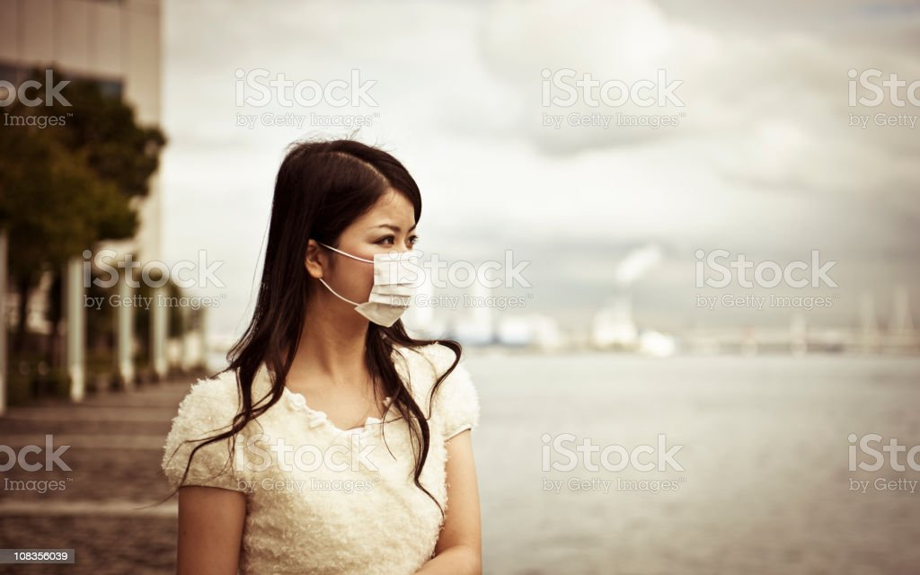 Asian woman wearing face mask with a blurred background stock photo