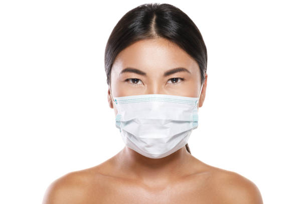 Asian woman wearing facial mask  for protection from air pollution or virus epidemic stock photo