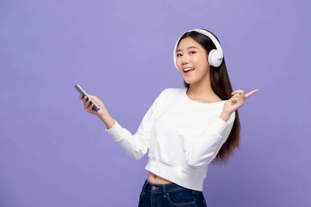 Asian woman wearing headphones listening to music from smartphone stock photo
