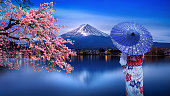 Asian woman wearing japanese traditional kimono at Fuji mountain and cherry blossom, Kawaguchiko lake in Japan.