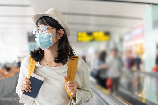 Happy Asian woman wear protective face mask and eyeglasses walking in international airport terminal during virus pandemic. Smiling Young Female traveler with yellow backpack at the departure hall