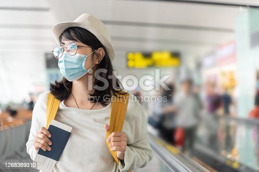 istock Asian woman wearing protective face mask in international airport. 1268389310