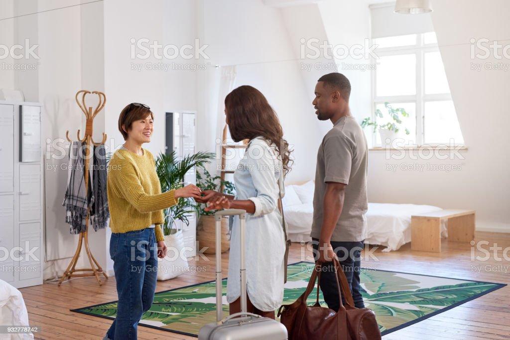 Mujer asiática da la bienvenida a joven pareja negra en su casa - foto de stock