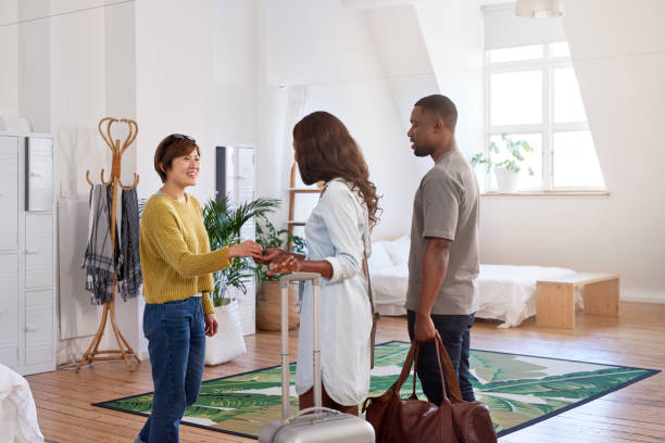 asian woman welcomes young black couple into her home - guest stock pictures, royalty-free photos & images