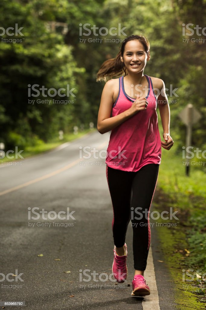 Asian woman were jogging on the road In the forest with sunny weather stock photo