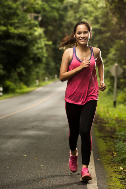 asian woman were jogging on the road in the forest with sunny weather - carpet runner stock photos and pictures