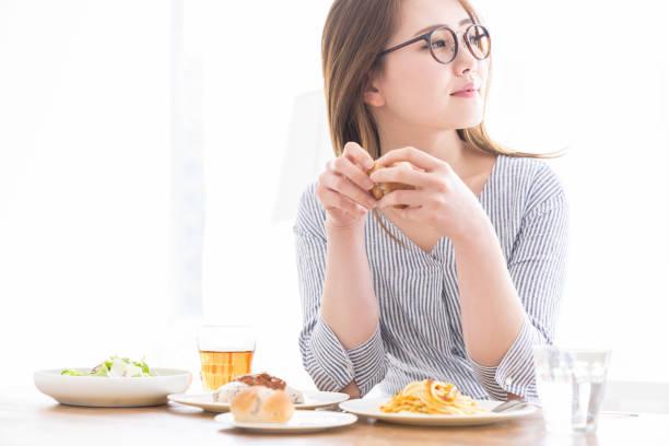 食べるアジアの女性 - people of color ストックフォトと画像