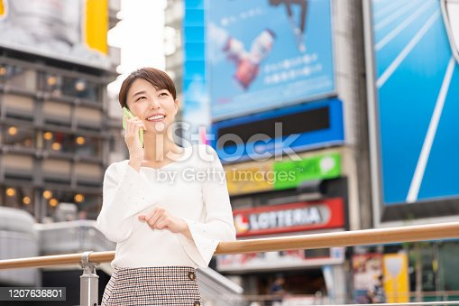 istock asian woman who travels in Osaka,telephone,Japan 1207636801