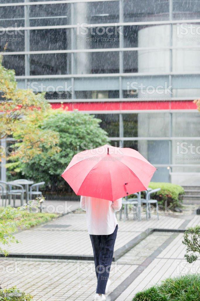 事務所ビルの庭に赤い傘とアジアの女性が歩いています。 ストックフォト