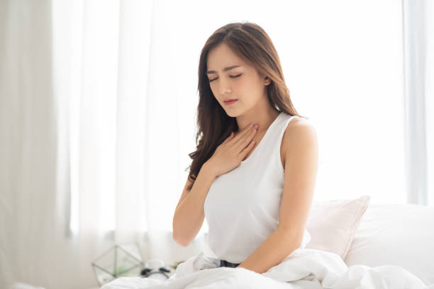 Asian Woman with Acid Reflux. Asian Beautiful Woman with Acid Reflux on her bed. Illness, Disease, Symptom. heartburn throat pain stock pictures, royalty-free photos & images