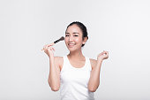 Portrait of attractive young Asian woman with beautiful skin holding brush for make up.