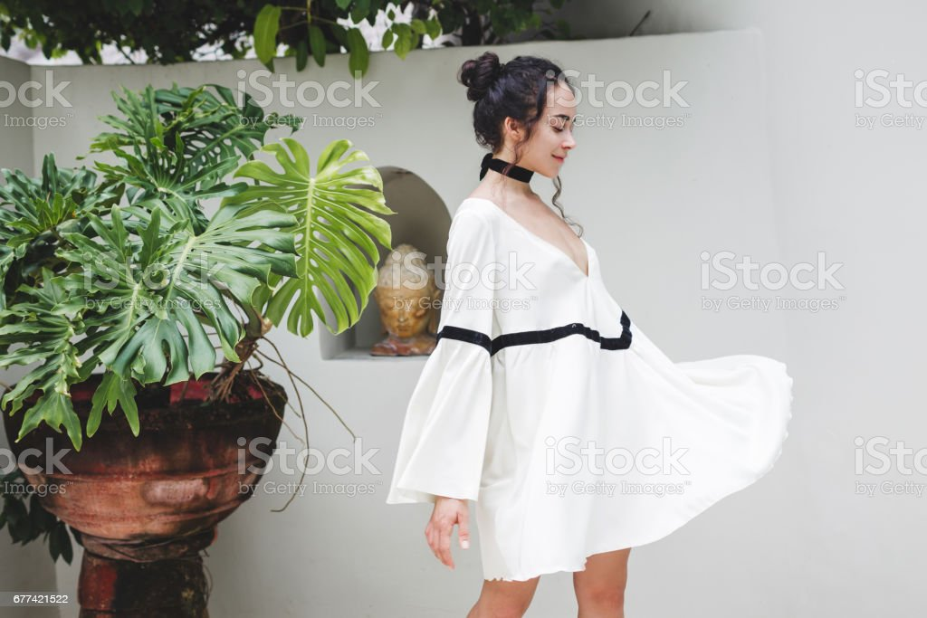 Asian woman with black curly hair enjoying in private villa in Canggu. Wearing white light tunic, barefoot. Casual style, tropical garden. Sunny weather stock photo