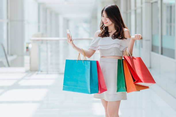 Asian woman with colorful shopping bag using smartphone stock photo