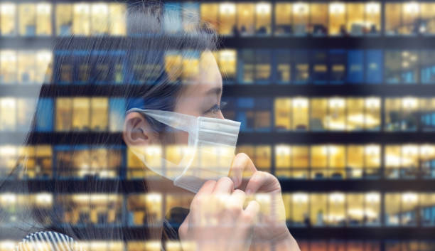 Asian woman with face mask going back to work, business building reflecting - foto stock