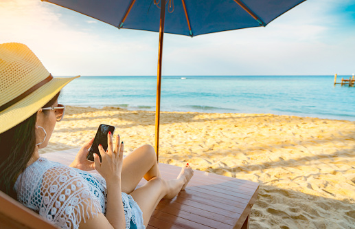 Asian woman with hat sit on sunbed under beach umbrella at sand beach and using smartphone on summer vacation. Girl in casual style relax and enjoy holiday at tropical paradise beach. Summer vibes.