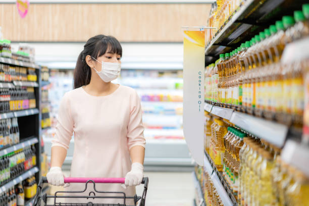 asian woman with hygienic mask and rubber glove with shopping cart in grocery and looking for cooking oil bottle to buy during covid-19 outbreak for preparation for a pandemic quarantine - palm oil bottles imagens e fotografias de stock