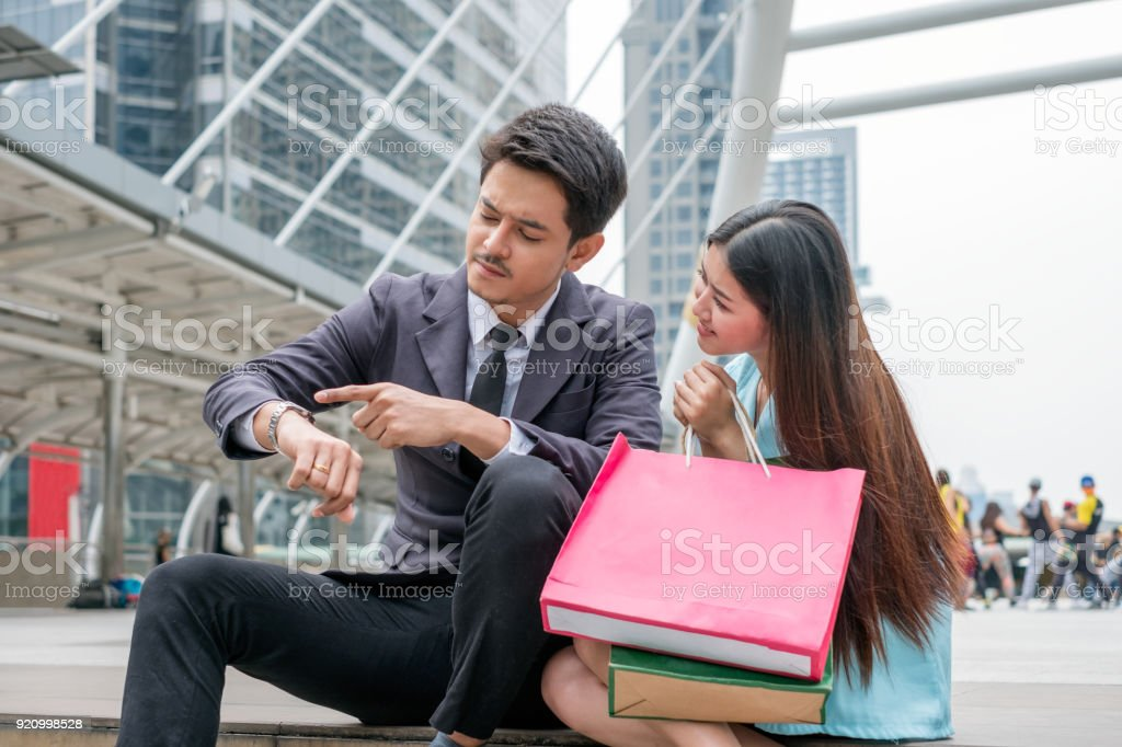 Asian woman with paper bag shopping plead with businessman finger point to watch stock photo