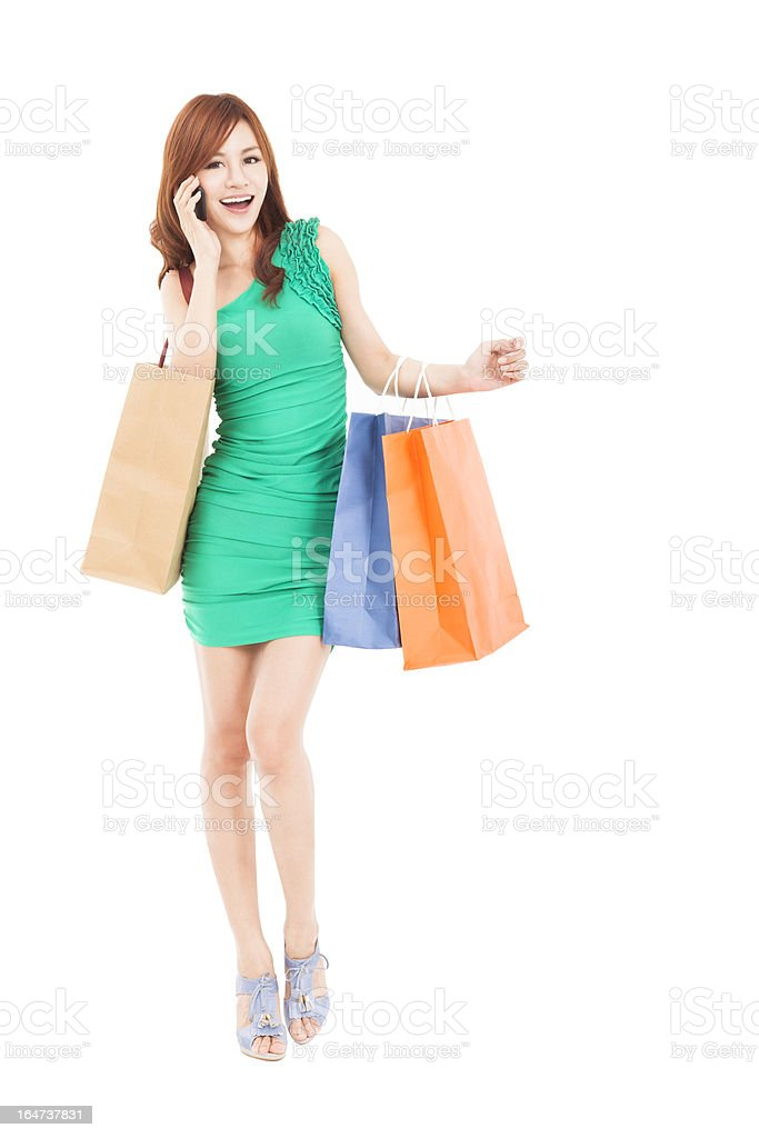 asian woman with shopping bags talking on the phone royalty-free stock photo