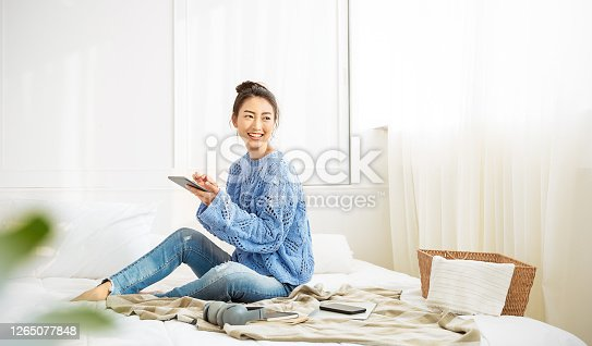 Asian woman with smile use tablet smartphone in blue winter sweater work home, Portrait young beauty asia girl relax in bedroom. Technology people connection digital online market banner