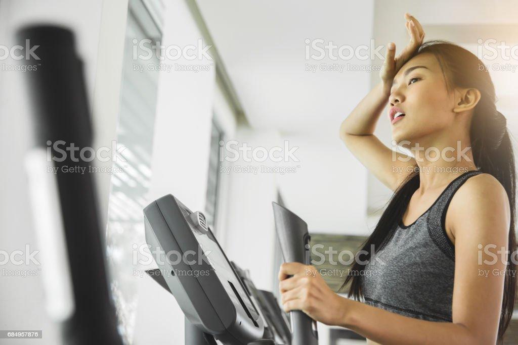 Asiatin mit Schweiß auf Ellipsentrainer Maschine im Fitnessstudio trainieren. Lizenzfreies stock-foto